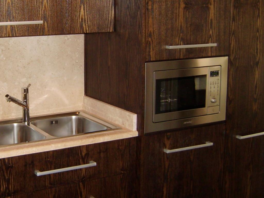 cucina dark in legno con forno colonna